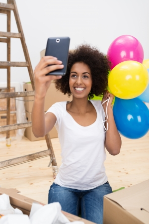 Happy African American woman taking a selfie with her mobile phone as she stands holding a bunch of colourful party balloons to celebrate the move to her new home