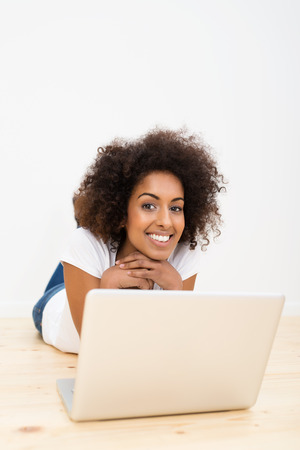 afro hairdo: Happy African American woman with a lovely frizzy afro hairdo lying on the wooden floor with a laptop computer smiling at the camera with a blank white wall and copyspace behind her