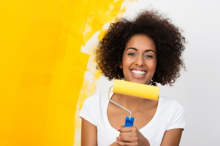 redecorating: Smiling African American woman redecorating her house holding a paint roller covered in orange paint which she has been applying to the wall behind her Stock Photo