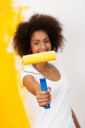 out of focus: African American woman with a paint roller covered in bright orange paint holding it out in front of her with a grin as she redecorates the wall behind her, focus to the roller Stock Photo