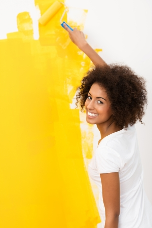 yellow walls: Happy young African American woman with a cute curly afro hairstyle painting a wall orange with a roller as she does home renovations