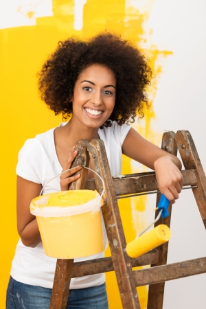 afro hairdo: Beautiful young African American woman with a frizzy afro hairdo doing home redecorating standing on a wooden stepladder with a paint roller and bright orange paint smiling at the camera