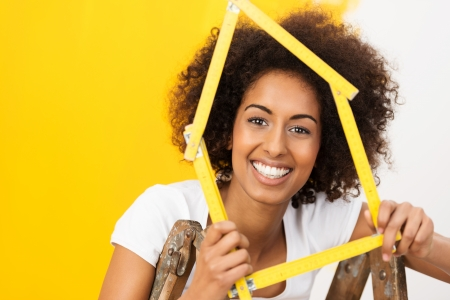Excited African American woman in her new home holding up a wooden frame in the shape of a house to celebrate her achievement as she stands in front of a half painted wall Zdjęcie Seryjne - 24991336
