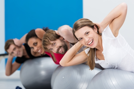 beautifu: Group of friends doing Pilates at the gym balancing on the gym balls with their hands behind their heads with focus to a beautifu laughing woman in the foreground