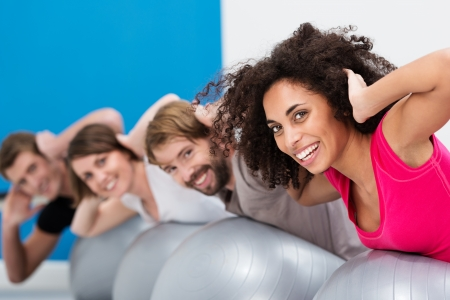 pilates man: African American woman in Pilates class at the gym with a group of her friends turning to smile happily at the camera during their workoput Stock Photo
