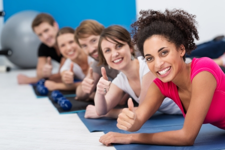Vivacious young people working out in the gym together in aerobics class lying on the floor on mats giving a thumbs up of approval with focus to a beautiful African American woman in the front