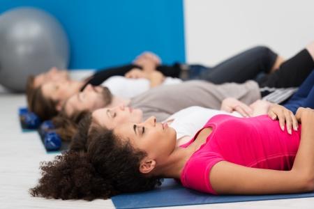 atmung: Aerobic-Kurs üben tiefe Atmung zur Entspannung auf dem Rücken liegend auf ihre Matten auf dem Boden mit Fokus auf eine junge afroamerikanische Frau in den Vordergrund