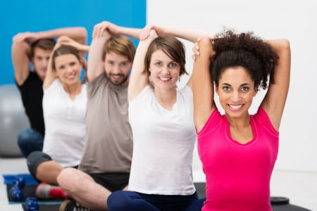 aerobics class: Diverse multiethnic group of fit young friends exercising together in class at the gym sitting cross legged on their mats doing stretching exercises Stock Photo