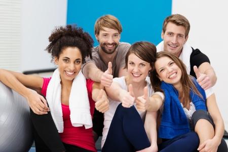 clase media: Grupo de diversos jóvenes atletas en el gimnasio sentado en las escaleras dando un pulgar hacia arriba de la aprobación como sonríen felizmente a la cámara Foto de archivo
