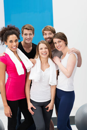workouts: Group of sporty diverse multiethnic young people at the gym posing together after their workouts with their towels around their shoulders