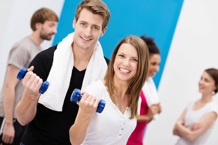 Enthusiastic young couple working out with dumbbells at the gym looking at the camera with beaming smiles in a health and fitness concept photo