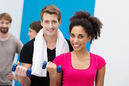 Attractive fit young multiethnic couple working out with dumbbells at the gym flexing their arms to tone their muscles photo