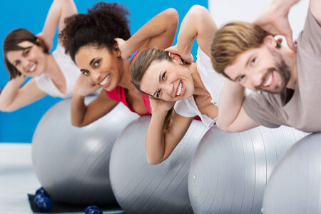 Diverse group of young riends having fun at the gym working out with gym balls doing Pilates exercises to tone their muscles turning to smile at the camera photo