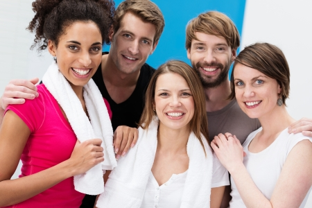 mixed race people: Group of happy multiethnic young friends posing together arm in arm after a workout at the gym looking at the camera with lovely friendly smiles Stock Photo