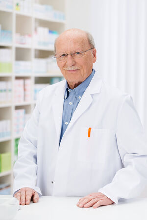 stocked: Confident senior pharmacist in his pharmacy standing behind the counter in front of stocked shelving smiling at the camera