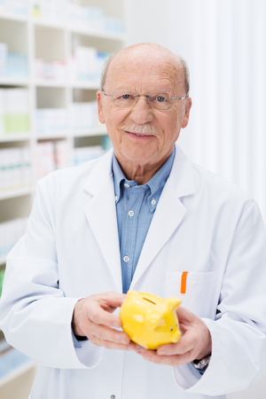 contemplates: Successful senior pharmacist holding a piggy bank with his savings as he contemplates taking retirement with his nest egg, conceptual image