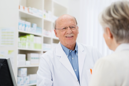 Elderly male pharmacist talking to a senior patient with a view over the womans shoulder to his face photo