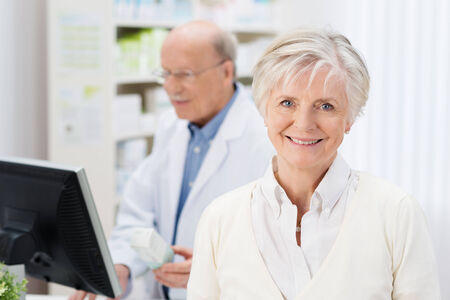 Friendly female pharmacist with a lovely smile greeting the viewer in the pharmacy with a colleague working  photo