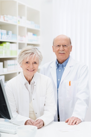 stocked: Two pharmacists standing behind the counter in the pharmacy in their white lab coats smiling at the camera in front of stocked shelves