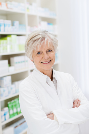 stocked: Happy confident mature female pharmacist standing in front of stocked shelves in the pharmacy with folded arms smiling at the camera Stock Photo