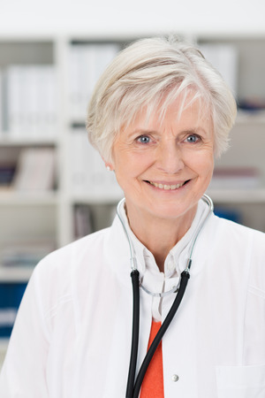 general practitioner: Smiling friendly attractive mature female doctor or General Practitioner standing in her office or surgery with shelves of files
