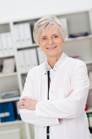 wise woman: Confident female doctor or nurse in an office standing in a white lab coat smiling at the camera with folded arms