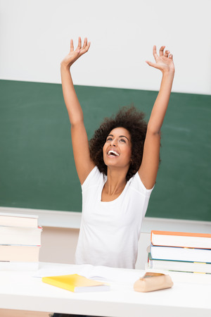 Young African American woman rejoicing stretching her hands into the air with a smile of joy and jubilation photo
