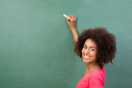 teachers: Beautiful African American student or teacher standing in front of the blank class blackboard with a piece of chalk in her hand ready to commence writing Stock Photo