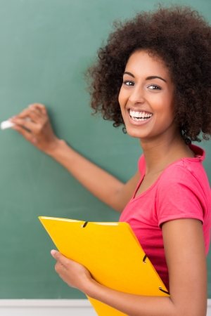 vivacious: Beautiful young African American student with an afro hairstyle and vivacious smile holding a file and writing on a blackboard