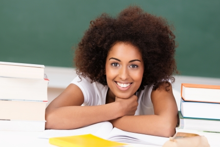 afro hairdo: Smiling attractive young African American student with an afro hairdo sitting between two piles of her text books Stock Photo