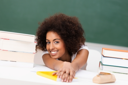 Relaxed young African American student with an afro hairstyle and lovely smile sitting at her desk between piles of books photo