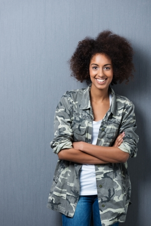 Smiling self-assured young African American woman standing leaning against a grey wall with her arms folded smiling at the camera photo