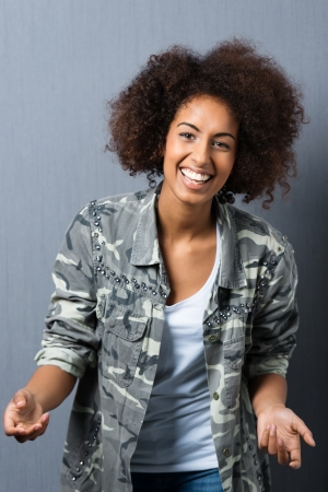 Trendy young African American woman with an afro hairstyle laughing as she stands leaning towards the camera photo