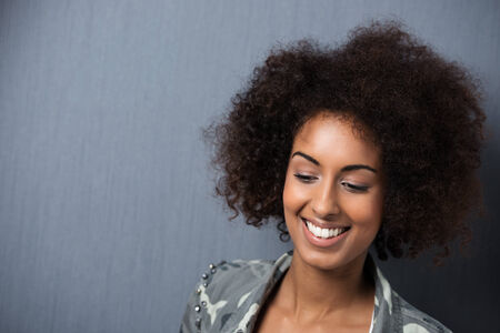 Smiling young African American woman with downcast eyes and a wild afro hairstyle against a dark grey with copyspace photo