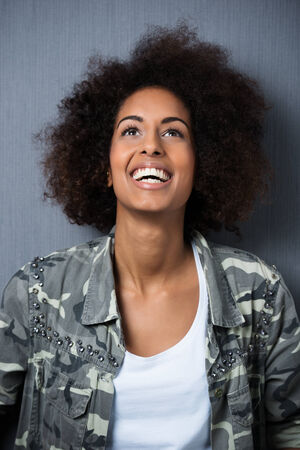 Joyful young African American woman with an afro hairstyle laughing and enjoying a good joke as she looks up into the air photo