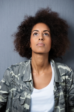 deep thought: Serious African American woman with an afro hairstyle staring pensively up into the air deep in thought Stock Photo
