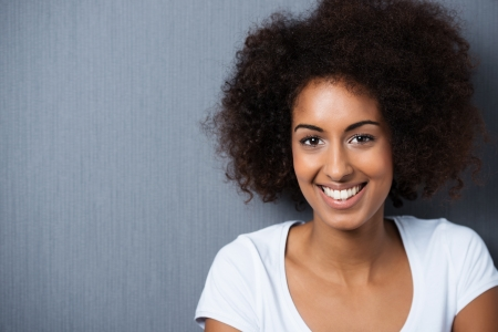 natural hair: Horizontal portrait of a cheerful African American attractive young woman, wearing a white T-shirt, while smiling with perfect teeth and looking at camera, on grey