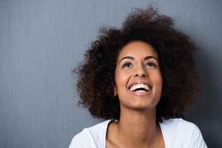 아프로 헤어 스타일과 미소 유머 감각을 가진 아프리카 계 미국인 여자 웃는 것은 그녀는 공중으로보고 다시 그녀의 머리를 기울어로