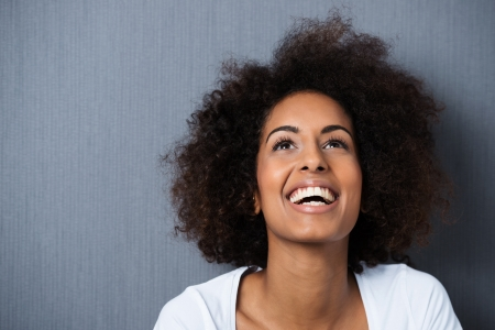 mujer: Riendo mujer afroamericana con un peinado afro y un buen sentido del humor sonriendo mientras se inclina la cabeza hacia atr�s para mirar hacia el aire Foto de archivo
