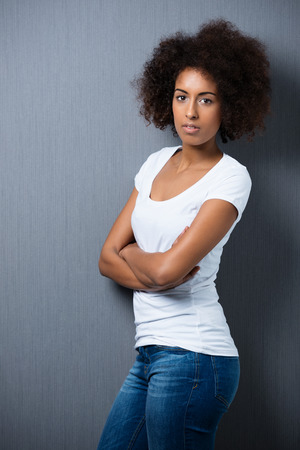 Serious young African American woman with an afro hairstyle standing sideways to the camera with folded arms on a grey  photo