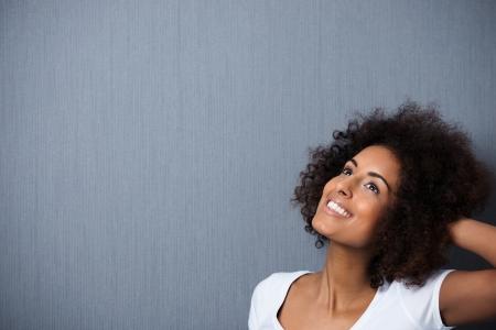 mujeres negras: Joven y bella mujer africana de pie americano so�ando despierto con la mano a su pelo afro rizado y una sonrisa caprichosa de placer mientras ella mira hacia arriba en el aire, con copyspace