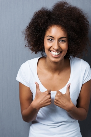 Vertical portrait of a happy young African American woman, wearing a white T-shirt while smiling and showing thumbs up, sign of acceptance, approval or encouragement photo