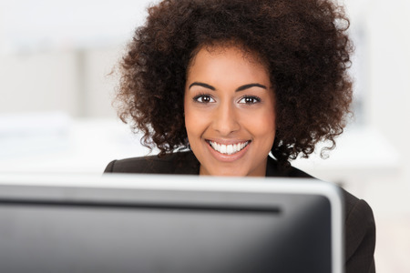 warmly: Beautiful happy African American woman with a curly afro hairstyle smiling warmly over the top of her computer monitor at the camera, closeup head portrait