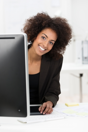 afro hairdo: Cute African American businesswoman with a wild afro hairdo and friendly smile peering around her computer monitor at the camera Stock Photo