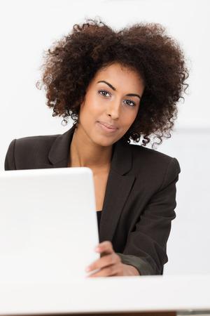 Modieuze Afrikaanse Amerikaanse onderneemsterzitting bij haar bureau met een laptop computer die de camera met een glimlach bekijkt