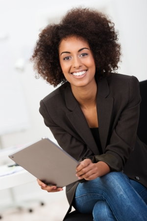 Friendly African American businesswoman with a beautiful smile and afro hairstyle sitting holding a tablet computer looking at the camera