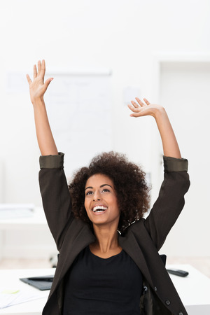 jubilation: Successful emotional African American businesswoman rejoicing in triumphant jubilation as she raises her hands in the air and cheers