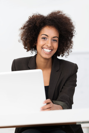 Happy African American businesswoman or student with an afro hairstyle sitting at a table with a laptop computer looking at the camera with a friendly smile photo