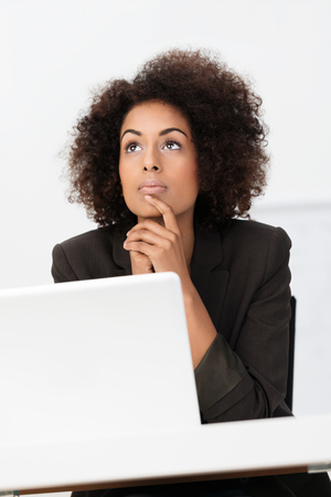 ethnic attire: Beautiful young African American businesswoman sitting thinking staring upwards with a pensive expression as she plans her business strategy