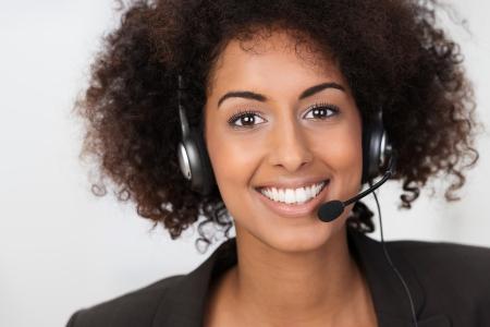 Cerrar un retrato facial de una hermosa vivaz empresaria estadounidense usando un auricular sonriendo a la cámara conceptual de los servicios al cliente, soporte o un operador de call center Foto de archivo